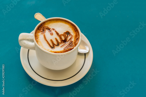 Cappuccino on a cup with foam and above the foam the inscription Cuba on a background