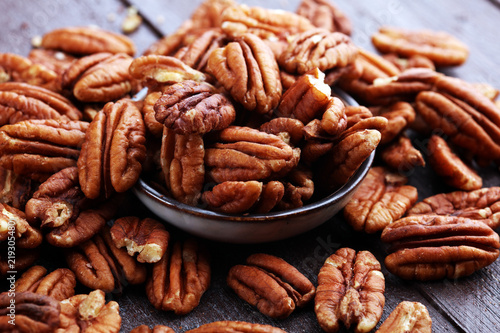 Poster Graine, aromate Pecan nuts on a rustic wooden table and pecan nuts in bowl