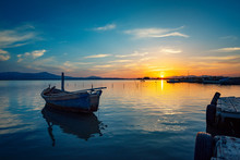 Fisherman Boat At Sunset On The Calm Lagoon With Perfect Water Reflections