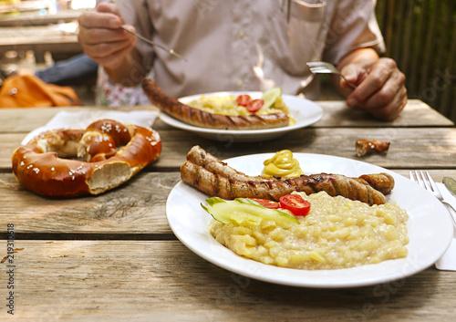 Fotografie, Obraz  Bavarian beer garden typical food: big pretzel, grilled sausages and potato sala