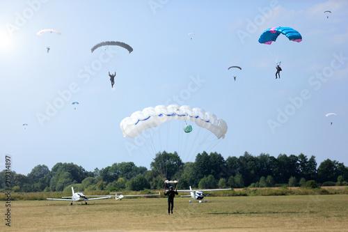 Spadochroniarze lądują na płycie lotniska aeroklubu, samoloty w tle.