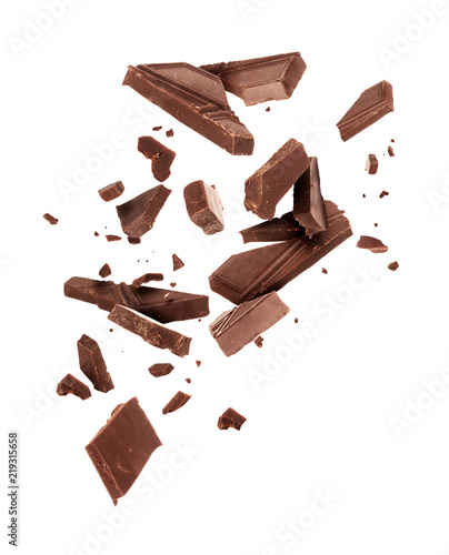 Fotografiet Pieces of dark chocolate falling close up on a white background