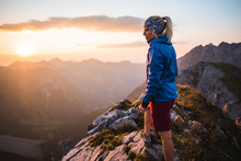A Young Adventurous Sportive Girl Enjoying A Beautiful Sunset On Top Of A Peak In The Austrian Alps