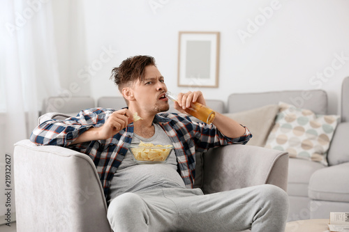 Obraz na plátně  Lazy man with bottle of beer and chips watching TV at home