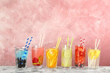 Glasses With Lemonades On Table Against Color Background