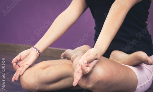 Hands of woman in chin mudra while sitting in lotus pose. Female yogi in padmasana. Lady practicing yoga meditation indoors. Calm, peaceful, breathing exercise, focus concepts. Vintage effect