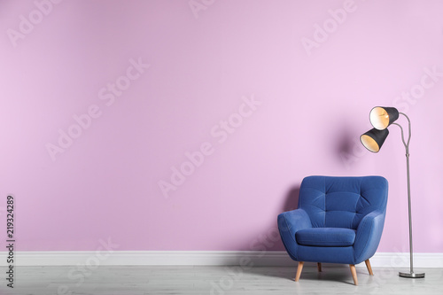 Comfortable armchair and lamp near color wall with space for text Tableau sur Toile