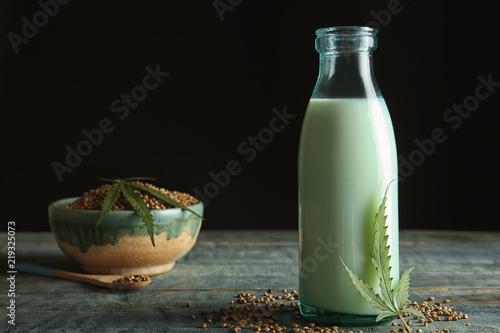 Bottle of hemp milk on wooden table