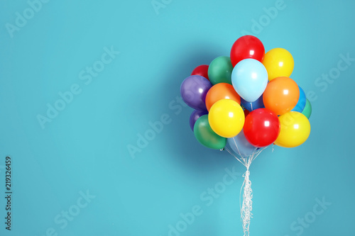 Fotografía Bunch of bright balloons and space for text against color background