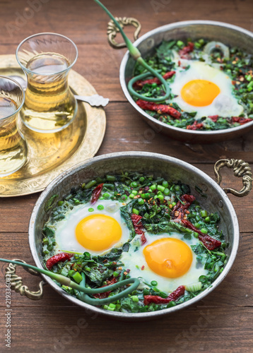 Aluminium Prints Food Green shakshuka. Fried eggs with fresh spinach, ramson, leek in a pan on a gray background, top view