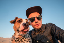 Spoiled Self Portrait Concept: Man Trying To Make A Selfie With His Funny Dog. Young Male Person And Staffordshire Terrier Posing For A Selfie Outdoors