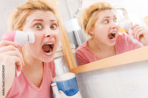 Shocked woman using facial cleansing brush #219343847