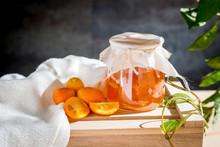 Kumquat And Jams On Wood Surface
