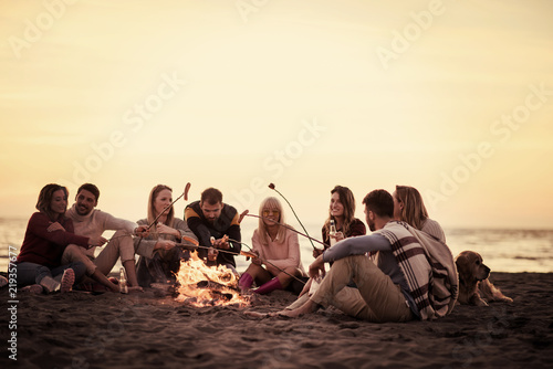 Cuadros en Lienzo Group Of Young Friends Sitting By The Fire at beach
