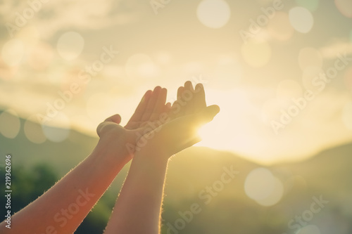 Fototapeta  Woman hands place together like praying in front of nature green  background