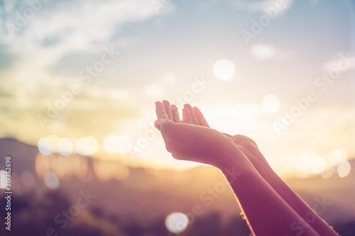 Vászonkép Woman hands place together like praying in front of nature green  background