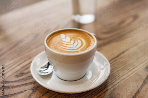 Latte art in cappuccino coffee cup at cafe table Canvas Print