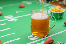 Pouring Beer Into Glass Mug On Table Decorated For Big Football Game