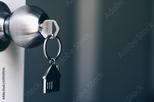 Property Concept, Home key with metal house keychain in keyhole Canvas Print