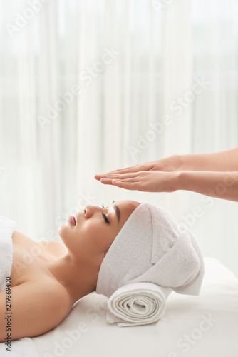 Photo  Palms of therapist over head of pretty Vietnamese woman