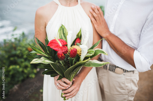 Slika na platnu Bouquet with red and green tropical flowers in bride's hands