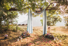 Sunset Wedding Ceremony, Arch Decorated With Grey Cloth Hanging On Big Tree And Rose Flowers Arrangement