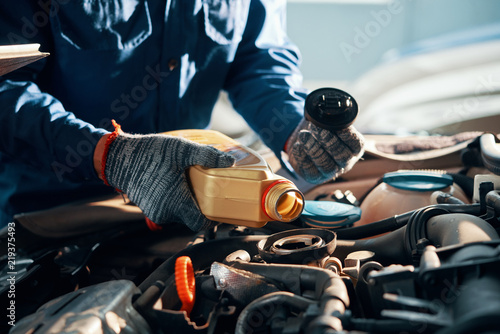 fototapeta na drzwi i meble Hands of mechanic pouring a bottle of oil in car engine