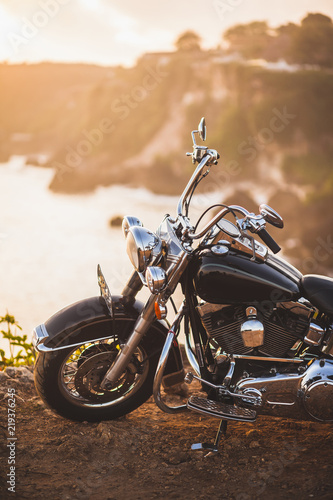 Fotobehang Fiets Old vintage motorcycle standing on the edge of cliff in warm sunlight at sunrise, shiny details of bike close-up