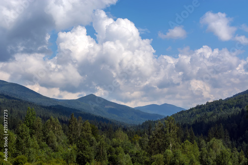 In de dag Bleke violet landscapes of mountains covered with dense coniferous forest, against a blue sky with clouds