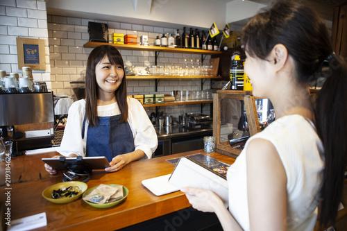 Foto 笑顔のカフェ店員とお会計をしようとする女性