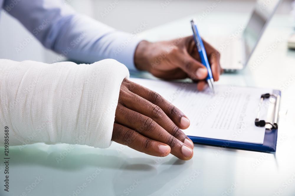 Fototapeta Injured Man Filling Insurance Claim Form