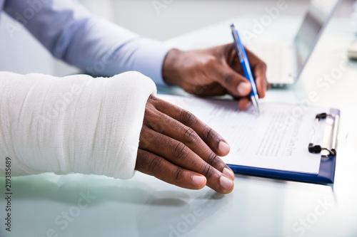 Obraz Injured Man Filling Insurance Claim Form - fototapety do salonu