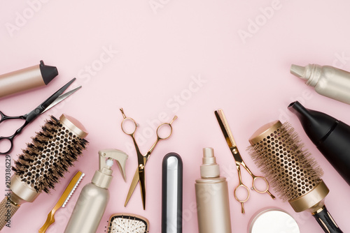 Various hair dresser tools on pink background with copy space