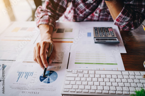 Tela Businessman working on calculator to calculate business data the financial report