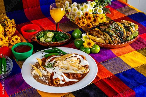 Fototapeta Enchiladas de mole con pollo y tacos de carnitas, comida mexicana en una mesa co