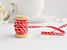 Red Diagonal Ribbon And Wooden Spool