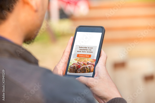 Food blog subscription concept. Man holding smartphone doing subscribe food blog on screen.