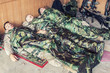 canvas print picture - Tired U.S. marines resting at temporary base or camp, lying on floor in uniform and tactical ammunition, covered with poncho liners and sleeping bags, sleeping well after hard raid, exhausting mission