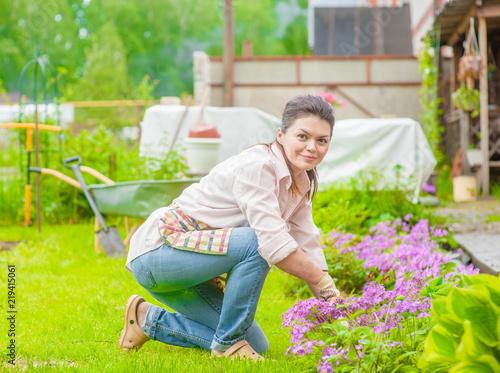 Keuken foto achterwand Begraafplaats woman working in the backyard, caring for flowers