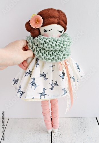 Lovely handmade doll wearing cute white dress, pale pink gaiters and wool scarf Fototapet