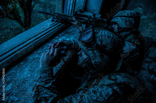 Marines sniper team armed with large caliber, anti-materiel sniper rifle hiding in ruined urban building, shooting enemy targets on range from shelter, sitting in ambush at night Canvas Print