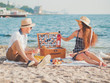 Young couple spending time on date together on the beach. Boyfriend and girlfriend on picnic. They relaxing, love each other. Relationship concept.