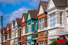 A Row Of Colourful Terraced Houses In London With With A LET Sign