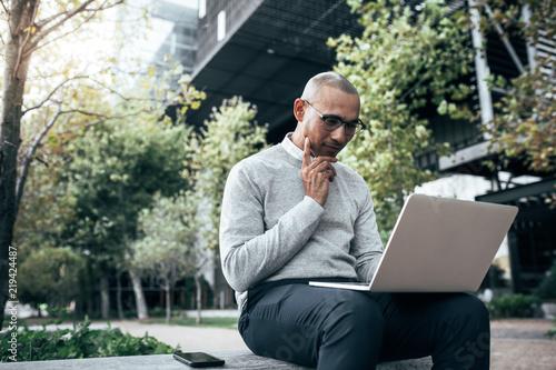 Obraz Businessman managing business working on laptop computer sitting - fototapety do salonu