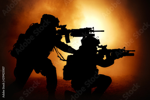 Canvas Prints Military Silhouettes of two army soldiers, U.S. marines team in action, surrounded fire and smoke, shooting with assault rifle and machine gun, attacking enemy with suppressive gunfire during offensive mission