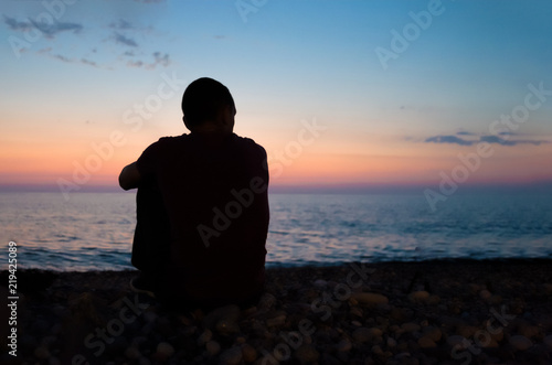 Fototapeta the man is sitting on the seashore and watching the sunset