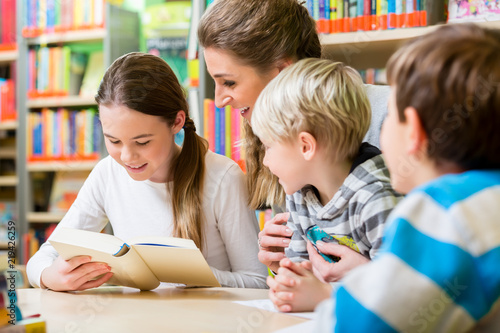 Vászonkép Lehrerin mit ihrer Klasse liest Bücher in der Bibliothek