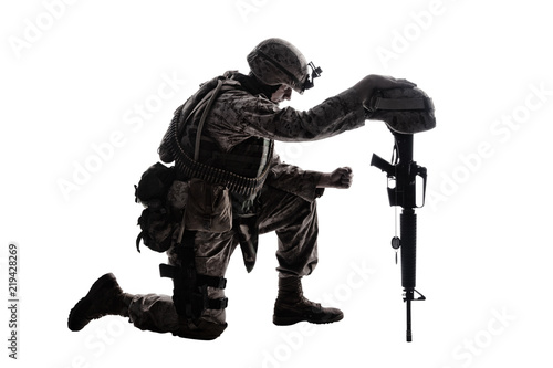 Fotografía  Army soldier in sorrow for fallen comrade, standing on knee, leaning on rifle with helmet and two dog tags on chain, studio shoot isolated on white low key silhouette