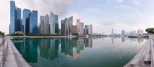 Photographie  Singapore's Central Business District skyline at sunrise, with high rise buildings and waterfront, from Marina Bay terrace deck