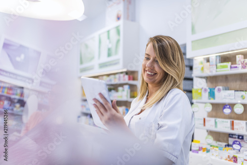 Tuinposter Apotheek Pharmacist working with a tablet computer in the pharmacy holding it in her hand while reading information